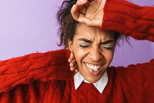 Ritratto di donna afroamericana tesa con acconciatura afro accigliata e afferrando la testa, isolata