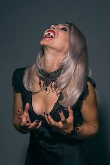 Ritratto di una donna vampiro con una bocca sanguinante e zanne di denti che celebra una vacanza diabolica felice halloween