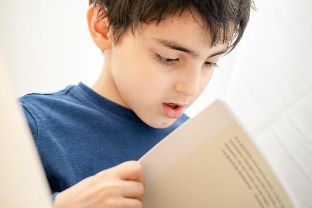 Il ritratto del bambino molto attento legge un libro interessante interesting