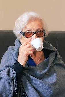 Ritratto di una donna molto anziana che beve caffè. positiva nonna novantenne.