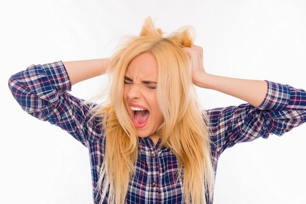 Ritratto di giovane donna molto frustrata che grida e che tiene i capelli