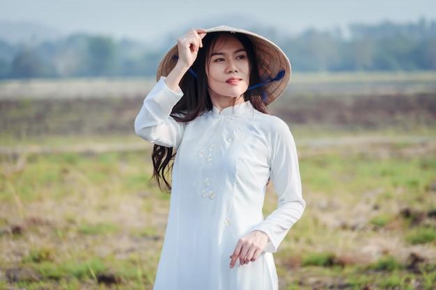 Ritratto di ragazza vietnamita in costume nazionale con cappello.