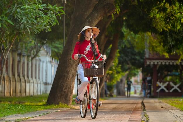 Ritratto del vestito rosso tradizionale dalla ragazza vietnamita, bella giovane donna asiatica che indossa il vietnam con la bicicletta