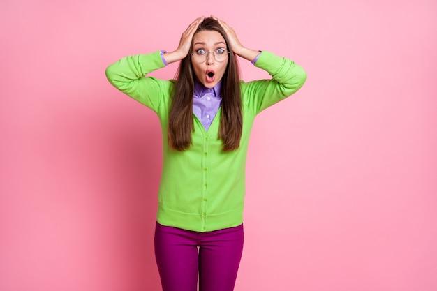 Ritratto di una ragazza stordita senza voce che tocca la testa con le mani urlando isolata su uno sfondo di colore rosa