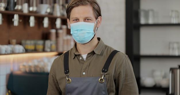 Il ritratto del lavoratore del cameriere indossa la maschera e guarda la telecamera al bar. il giovane barista attraente e bello in grembiule sta con fiducia al bar o al ristorante durante covid19.