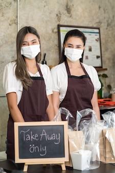 Ritratto di cameriera indossare maschera protettiva sorridente con segno di cibo da asporto o da asporto.