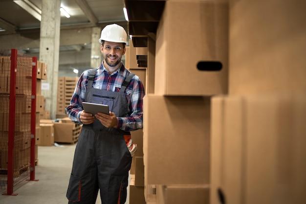 Ritratto di operaio di magazzino che tiene computer tablet e in piedi da scatole di cartone con merci nel magazzino di fabbrica.