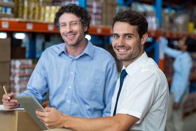 Ritratto dei magazzinieri che per mezzo della compressa digitale