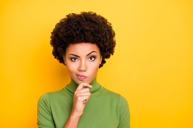 Ritratto di donna interessata dai capelli castani ondulati che fa smorfie toccando il mento con curiosità sul viso.
