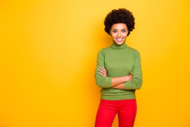 Ritratto di donna radiosa dentata allegra ondulata in pantaloni rossi con le braccia incrociate vicino allo spazio vuoto.