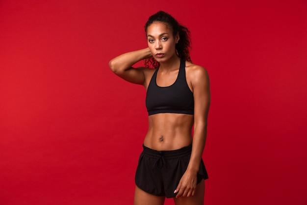 Ritratto di donna afroamericana ben costruita in abiti sportivi neri in piedi, isolata sopra la parete rossa
