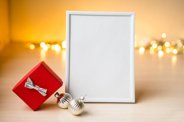 Mockup di cornice bianca ritratto sul tavolo con luci boken e decorazioni natalizie. foto di alta qualità