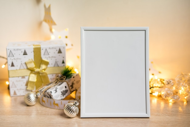Modello bianco della cornice del ritratto con i regali di natale, luci boken foto di alta qualità