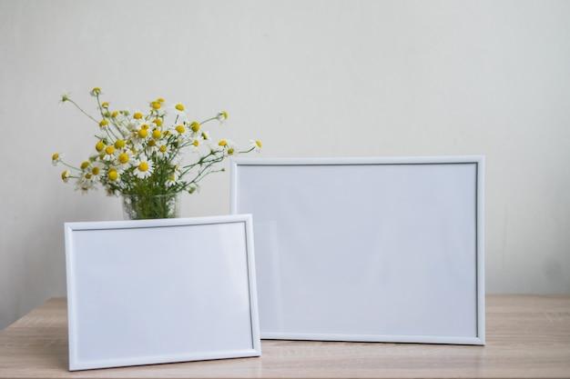 Modello bianco della cornice del ritratto sul vaso di vetro della tavola di legno con la camomilla