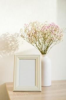 Mockup di cornice immagine ritratto bianco sulla tavola di legno. vaso moderno in ceramica con gipsofila. sfondo muro bianco. interni scandinavi. verticale.