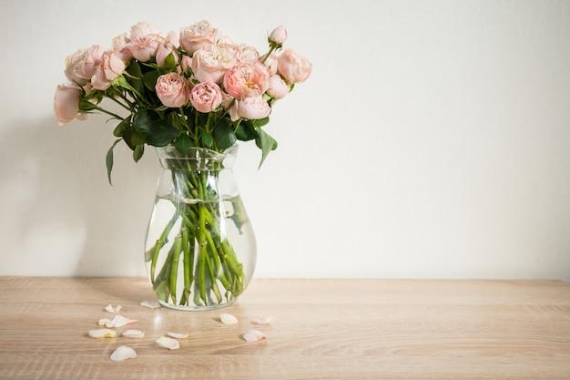 Mockup di cornice immagine bianco ritratto su tavola di legno vaso moderno in ceramica con rose sfondo muro bianco interni scandinavi
