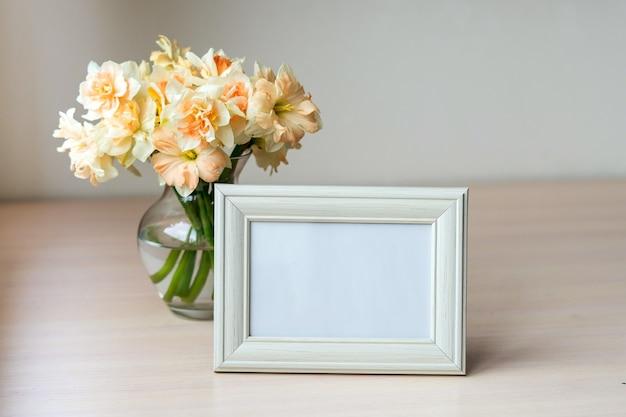 Portafoto bianco ritratto su tavola in legno vaso moderno in vetro con narcisi