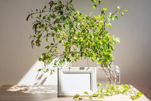 Cornice bianca ritratto su tavola di legno vaso di vetro moderno con rami verdi eco lifestyle