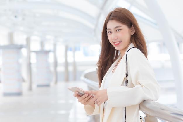 Ritratto con sfondo sfocato di capelli lunghi bella giovane donna asiatica professionale in abito bianco