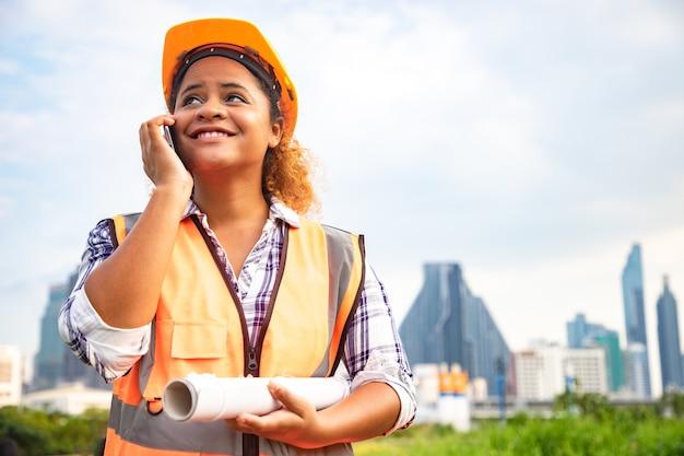 Ritratto di donna architetto in piedi con disegni costruttivi rotolo di carta e comunicazione tramite smartphone.
