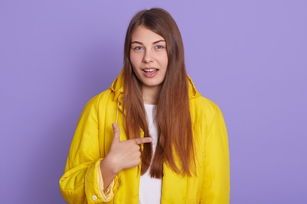 Ritratto di donna che ti chiede di parlare con me, intendi me, bella donna che punta a se stessa isolata su sfondo lilla, indossando una giacca gialla casual.
