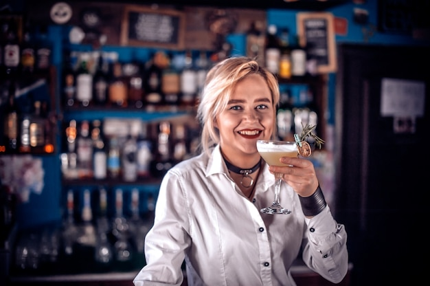 Ritratto di donna barista pone gli ultimi ritocchi su un drink mentre si trova vicino al bancone del bar in pub