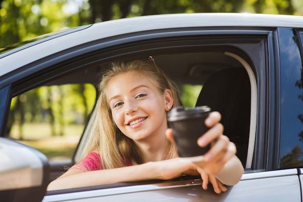 Ritratto di donna in auto con bicchiere di carta