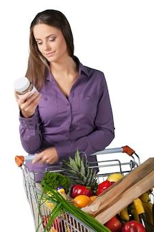 Ritratto di una donna che controlla l'etichettatura degli alimenti con il carrello della spesa