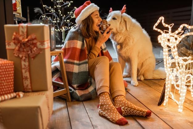 Ritratto di una donna con cappello natalizio e plaid con il suo simpatico cane che celebra le vacanze di capodanno sulla terrazza splendidamente decorata di casa, dando da mangiare al cane con biscotti di pan di zenzero