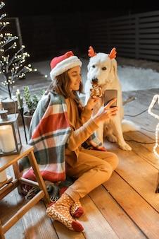 Ritratto di una donna con cappello natalizio e plaid con il suo simpatico cane che celebra le vacanze di capodanno a casa, nutrendo il cane con biscotti di pan di zenzero e facendo selfie foto