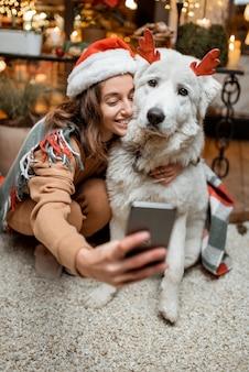 Ritratto di una donna con cappello natalizio con il suo simpatico cane che celebra le vacanze di capodanno sulla terrazza splendidamente decorata di casa, facendo foto selfie insieme