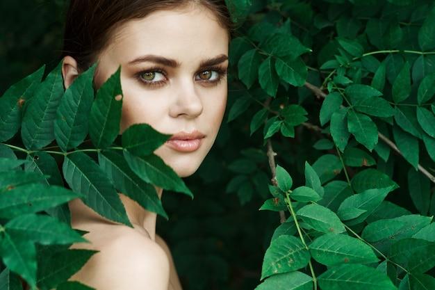 Ritratto di una donna cosmetologia natura foglie verdi modello glamour