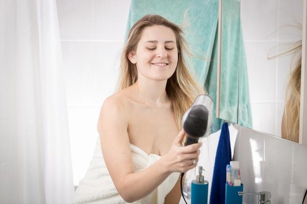 Ritratto di donna che copre in asciugamano asciuga capelli