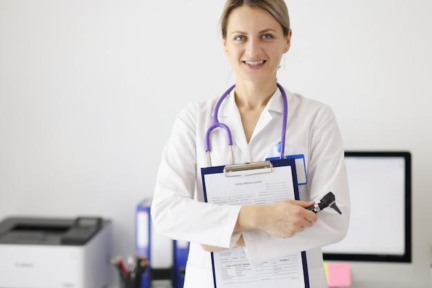 Ritratto di donna medico con documenti medici e otoscopio nelle sue mani