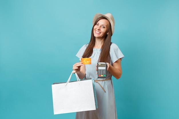 Ritratto di donna in abito, cappello con pacchi borse con acquisti dopo lo shopping, terminale di pagamento bancario moderno wireless per elaborare e acquisire pagamenti con carta di credito isolati su sfondo blu pastello.