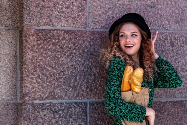 Ritratto di donna vestita in stile francese con baguette in mano. stile francese di parigi. primo piano della donna francese in abiti eleganti che tengono baguette fresche e sorridente. posto per un'iscrizione o un logo