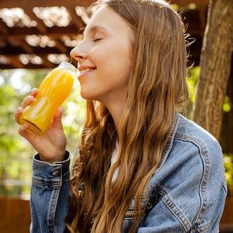 Ritratto di donna che beve dalla bottiglia di succo di frutta fresco