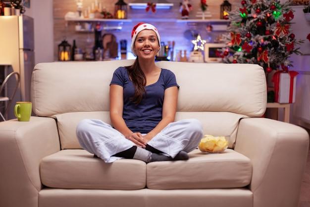 Ritratto di donna che indossa un cappello rosso da babbo natale seduto nella posizione del loto sul divano