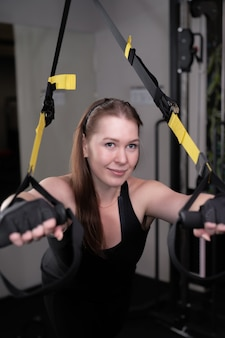 Ritratto di una donna che si esercita in una palestra e accovacciata