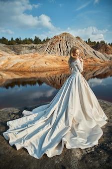 Ritratto di una donna sul favoloso paesaggio in montagna, un matrimonio in natura, ragazza in abito lungo