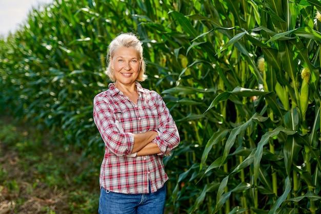 Ritratto di una contadina in un campo di mais. contadina che raccoglie mais.