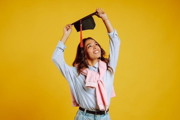 Ritratto di donna in un cappello di laurea sulla sua testa in posa sul giallo.