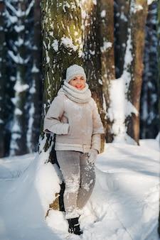 Ritratto di una donna in vestiti grigi in una foresta di inverno. ragazza nella foresta innevata del nuovo anno.