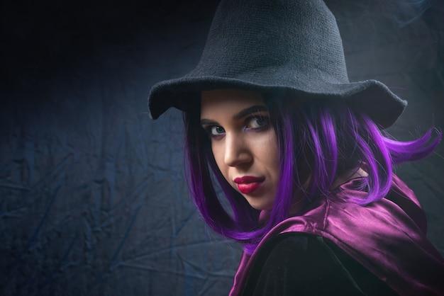 Ritratto di donna in costume di halloween con trucco luminoso e capelli viola in ombra su sfondo nero.