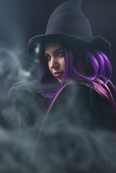 Ritratto di donna in costume di halloween con trucco luminoso e capelli viola