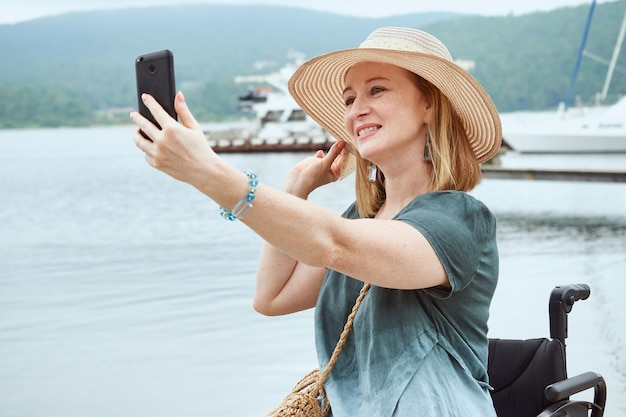 Il ritratto di una donna con un cappello fa un selfie sullo sfondo di un paesaggio marino.