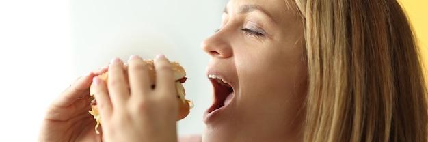Ritratto di donna che si diverte a mordere hamburger