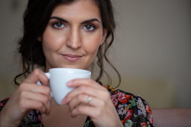 Ritratto di donna che tiene tazza con caffè in primo piano