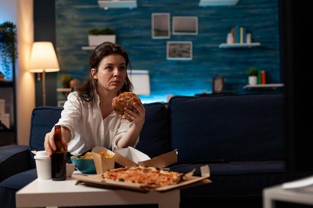 Ritratto di donna che tiene in mano un delizioso buger che mangia cibo da asporto per la consegna