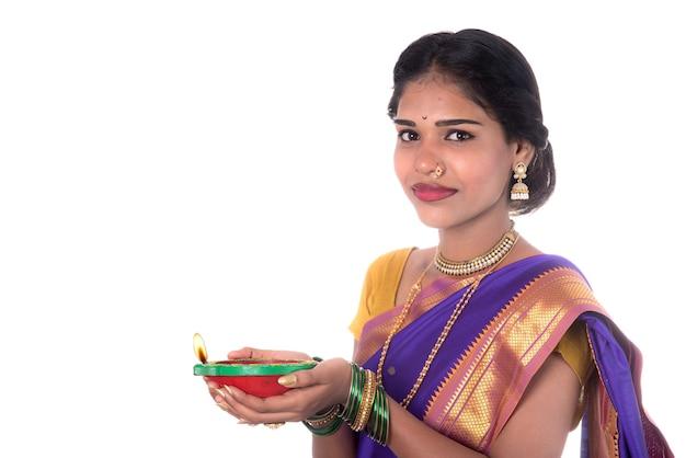 Ritratto di una donna che mantiene diya, diwali o deepavali foto con mani femminili tenendo la lampada a olio durante la festa della luce su sfondo bianco
